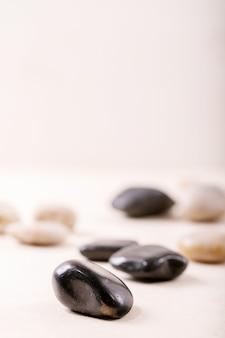 Pedras decorativas brancas e pretas e seixos sobre parede de madeira cinza