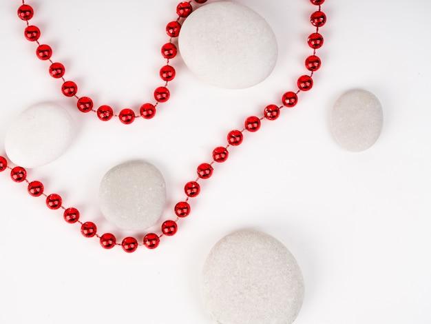 Pedras do mar branco e contas vermelhas entre eles. belas contas brilhantes vermelhas
