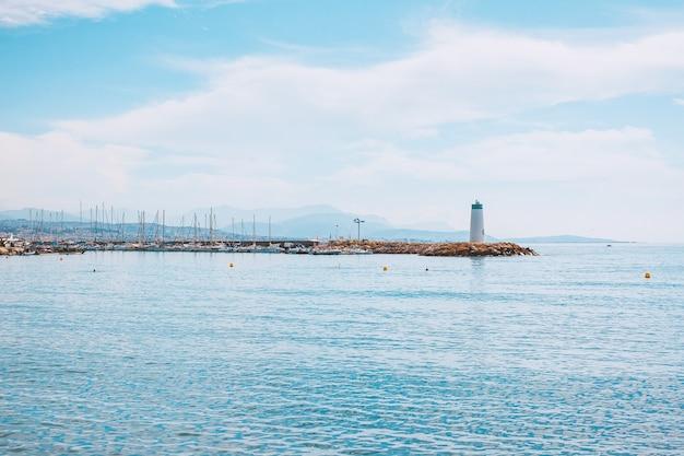Pedras do mar da marina da costa e farol na riviera francesa