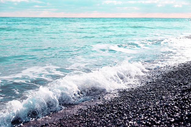 Pedras do seixo na costa de mar azul na luz do por do sol.