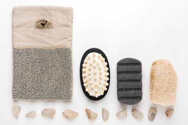Pedras dos termas arranjadas na fileira com bucha; escova de massagem; purificadores; pedra-pomes no fundo branco