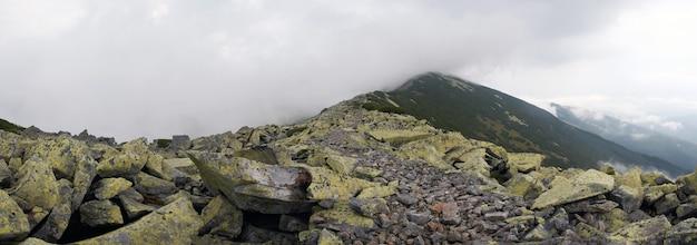 Pedras e nuvens na região de gorgany das montanhas dos cárpatos (ucrânia) e pássaros distantes no céu. imagem composta de seis tiros.