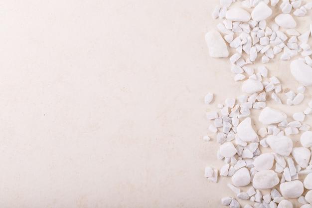 Pedras e pedras decorativas brancas como moldura sobre fundo branco de textura. layout criativo da natureza. espaço para design