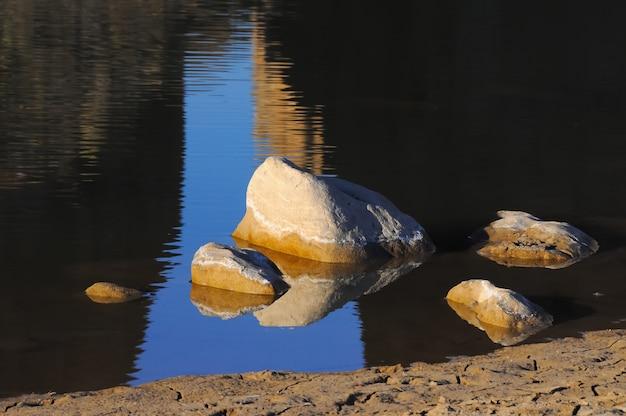 Pedras em um rio raso contra um reflexo azul do céu, texas, santa elena canyon, eua