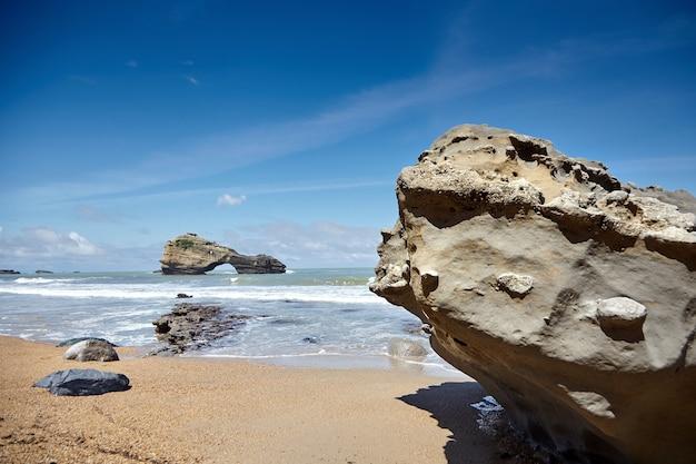 Pedras em uma praia arenosa e uma ilha rochosa. costa atlântica no sudoeste da frança. dia ensolarado de verão com céu azul