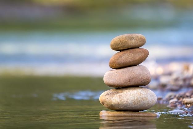Pedras equilibradas em uma pilha em águas rasas
