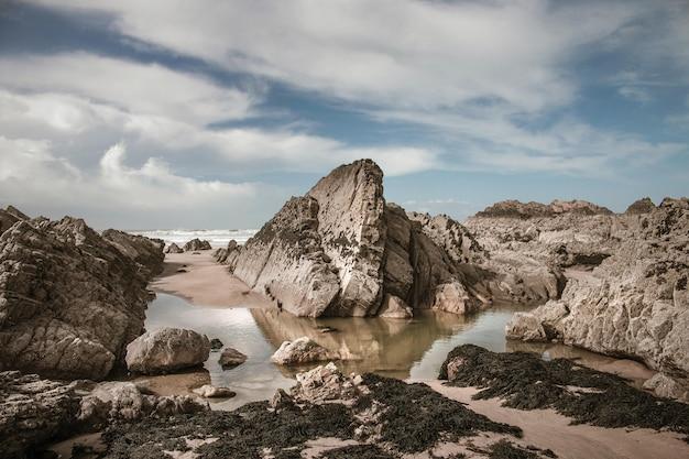 Pedras grandes e areia molhada na praia durante o dia