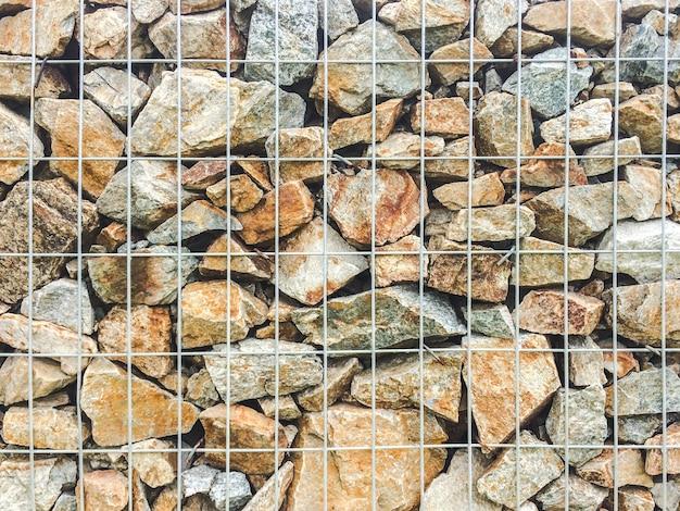 Pedras na gaiola de arame de metal, parede de gabião de pedra.
