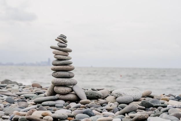 Pedras na praia em forma de uma pirâmide. equilíbrio e meditação, espaço para texto