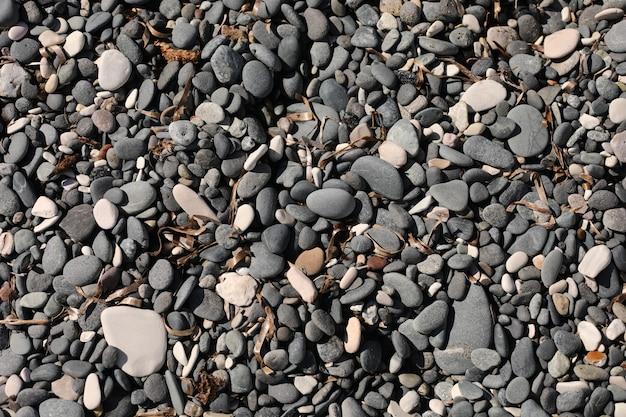 Pedras na praia. textura de pedra cascalho. praia de calhau ao ar livre natureza