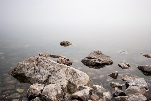 Pedras no lago no meio do nevoeiro. pedras grandes e pequenas. a água é transparente e sob a água você pode ver pedras cobertas de lodo. copie o espaço.