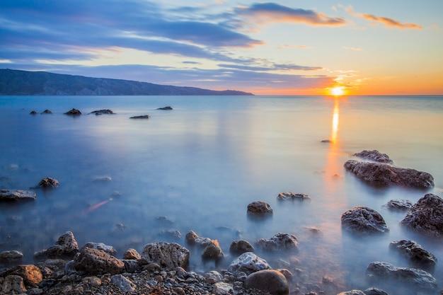 Pedras no oceano contra o pôr do sol, sobre o qual a névoa