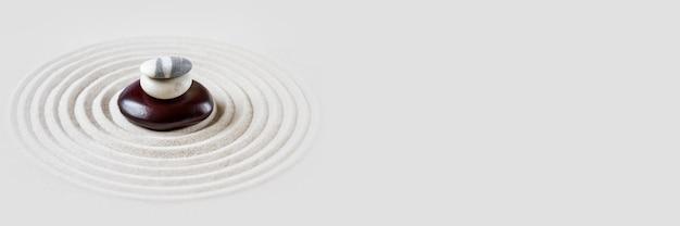 Pedras pretas e brancas na areia. cena de fundo do jardim japonês zen. banner horizontal