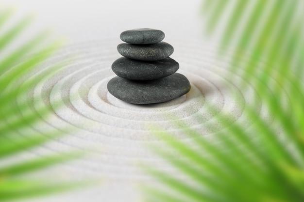 Pedras pretas se amontoam na areia atrás das folhas de palmeira. jardim zen japonês