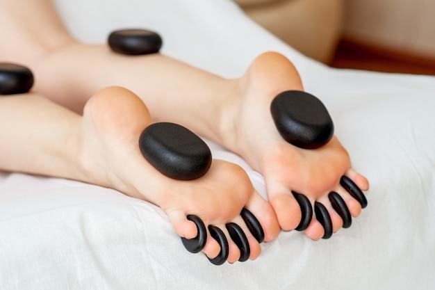 Pedras quentes, deitado sobre os pés femininos