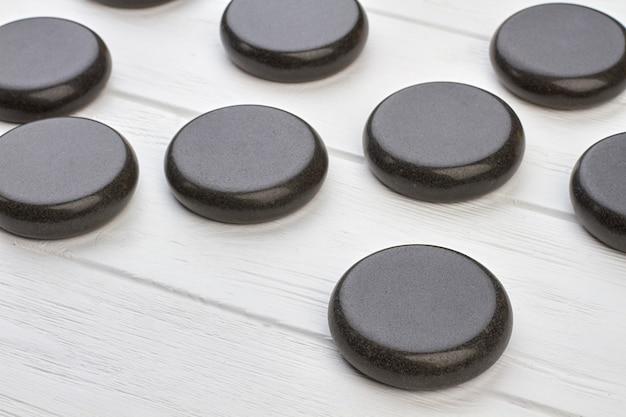 Pedras redondas polidas pretas de close-up na mesa de madeira branca. ímãs redondos escuros.