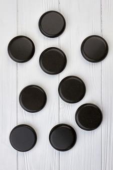 Pedras redondas polidas pretas na mesa de madeira branca. vista superior plana lay.