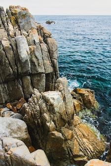 Pedras rochosas ásperas à beira-mar, costa da baía do oceano pacífico