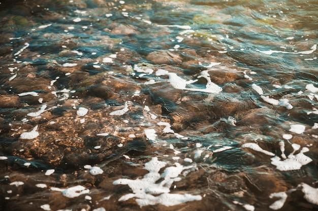 Pedras sob a ondulação da água