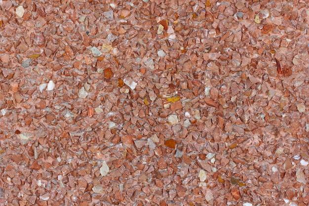 Pedras vermelhas e alaranjadas pequenas do fundo no emplastro na parede, estrutura uniforme.