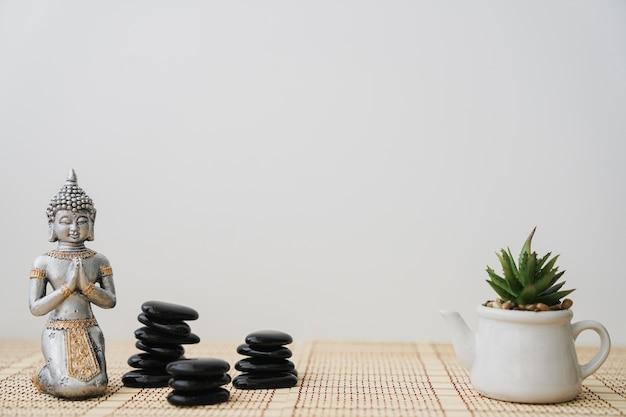 Pedras vulcânicas, buddha e vaso de flores