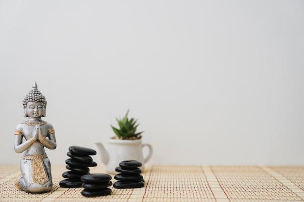 Pedras vulcânicas, figura buddha e pote de flores