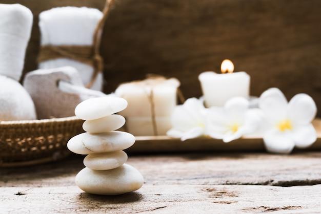 Pedras zen brancas e spa e tratamento com toalhas, esfoliante, sabonete de coco e flores de frangipani em fundo de madeira rústico