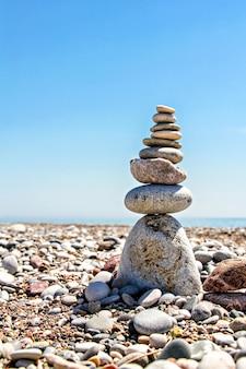 Pedras zen empilhadas na praia contra um céu azul e oceano com espaço de cópia