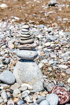 Pedras zen empilhadas na praia contra um fundo de areia e cascalho