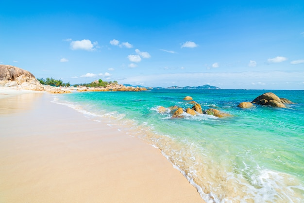 Pedregulhos exclusivos da rocha da água tropical turquesa lindo da praia transparente, destino de viagem da costa sudeste de cam ranh nha trang vietnã, céu azul claro