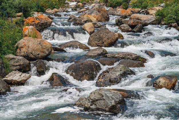Pedregulhos grandes em close-up de riacho de montanha. corredeiras do rio com espaço de cópia. fluxo de água rápido ao longo da bela vegetação. fluxo rápido perto de pedras molhadas. fundo de ondas limpas. rica flora das terras altas.