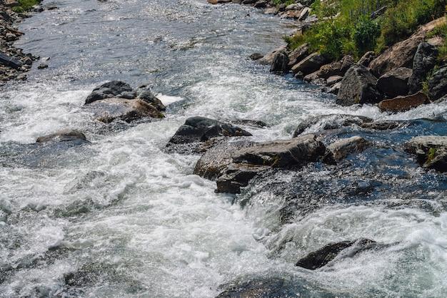 Pedregulhos grandes em close-up de riacho de montanha. corredeiras do rio rápido, com espaço de cópia. fluxo de água com espuma. fluxo rápido perto de pedras molhadas. fundo de ondas de agua potável. textura natural do fluxo brilhante do riacho