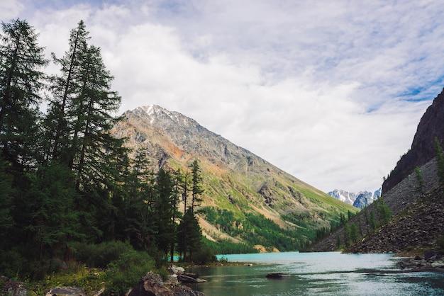 Pedregulhos grandes na água do lago da montanha na cena de montanhas gigantes