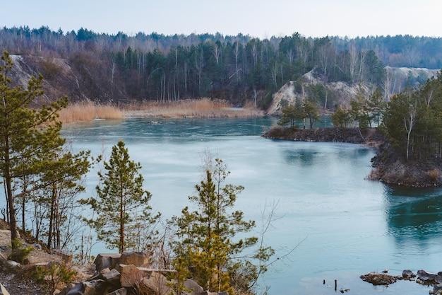 Pedreira bonita perto do lago coberto de gelo fino
