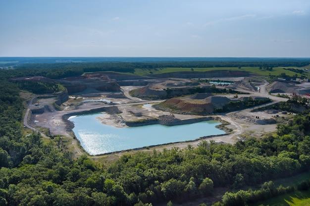 Pedreira de mineração com escavação a céu aberto em lago azul formado por atividades de mineração em vista aérea