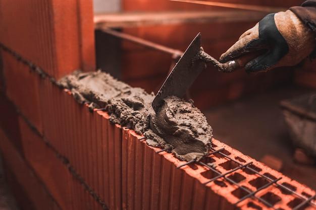 Pedreiro coloca tijolos para fazer uma parede