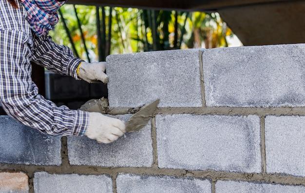 Pedreiro, colocando para baixo outra linha de tijolos no site