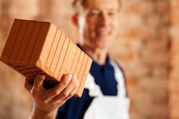 Pedreiro com tijolo no canteiro de obras