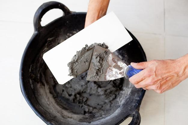 Pedreiro de construção pedreiro mãos com argamassa de cimento