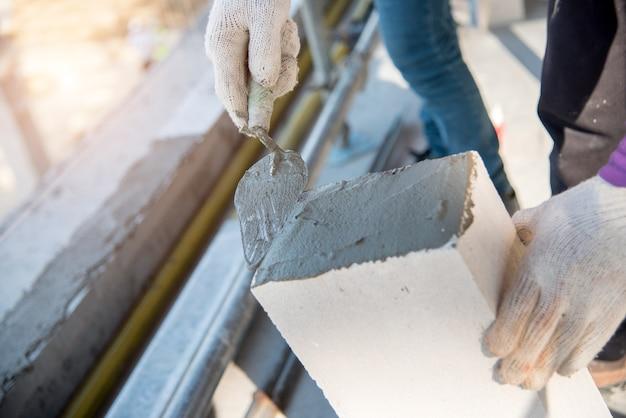 Pedreiro de trabalhador pedreiro construção instalando tijolo de silicato de cálcio