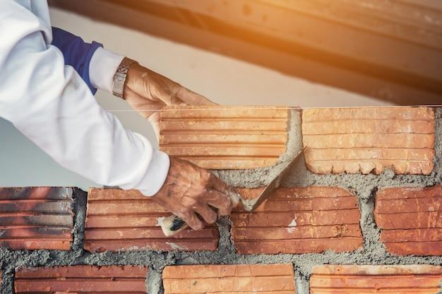 Pedreiro e rebocador de cimento, tijolo para construção