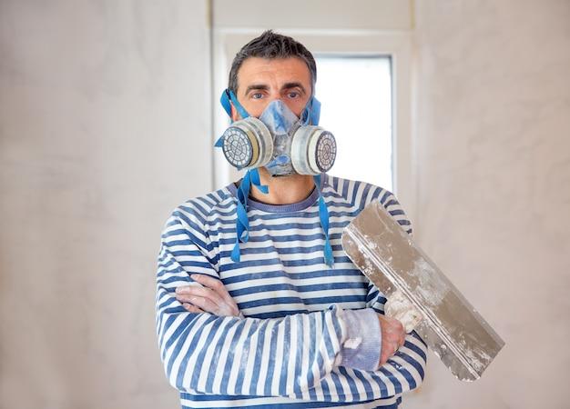 Pedreiro engraçado homem de reboco com máscara protetora e espátula
