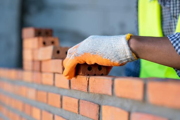 Pedreiro industrial que instala tijolos no canteiro de obras, trabalhador do pedreiro que instala a alvenaria de tijolo.