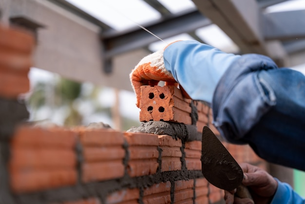 Pedreiro instalando alvenaria de tijolo na parede com espátula espátula no canteiro de obras