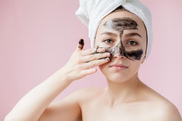 Peeling cosmético de beleza. closeup linda jovem fêmea com máscara preta peel na pele. close de uma mulher atraente com produto cosmético de peeling de cuidados da pele no rosto. alta resolução.