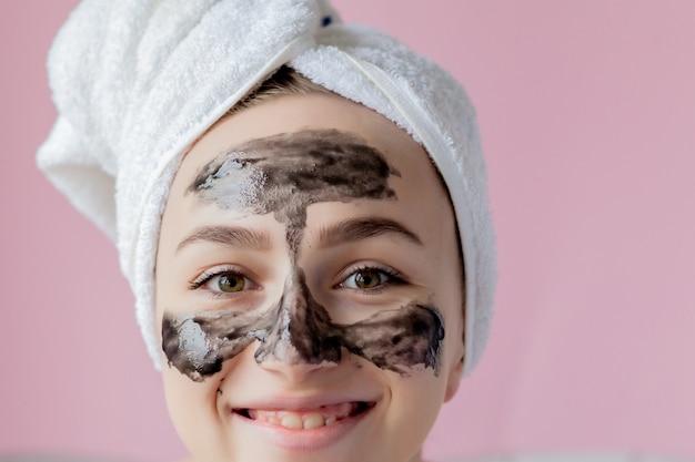 Peeling cosmético de beleza. closeup linda jovem fêmea com máscara preta peel na pele.