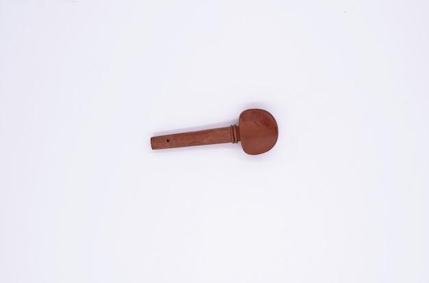 Pega de afinação para violino colocada sobre fundo branco, parte do violino acústico
