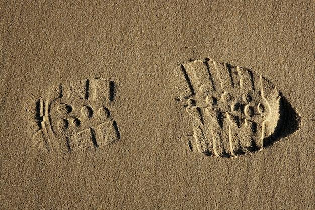 Pegada de sapato de bota sobre a areia da praia