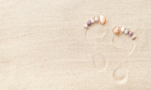 Pegada humana nua na areia com conchas, vista superior, espaço de cópia