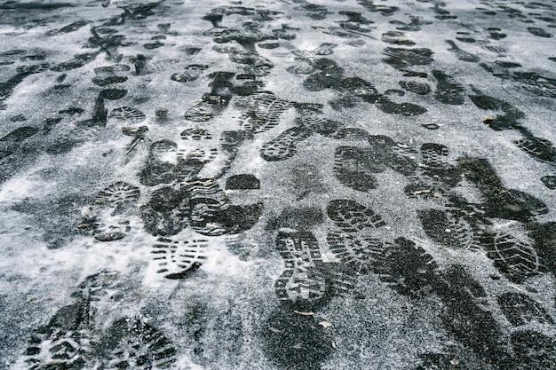Pegadas de pessoas na neve no asfalto no inverno